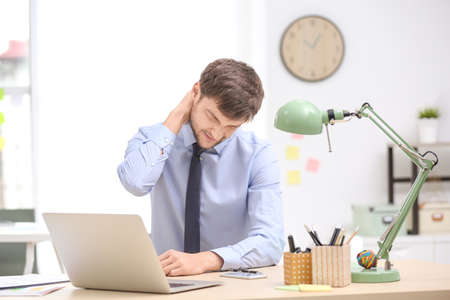 Young man suffering from neck pain in office