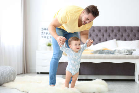 Photo pour Baby taking first steps with father's help at home - image libre de droit