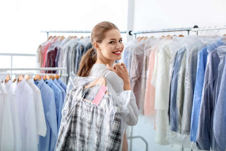 Young woman holding hanger with clothes in plastic bag at dry-cleaner's
