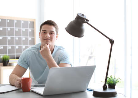 Portrait of confident young man with  laptop and cup at table