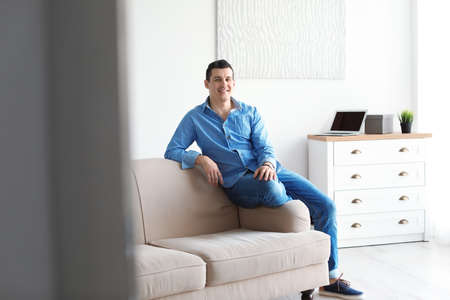 Portrait of confident man on sofa at home