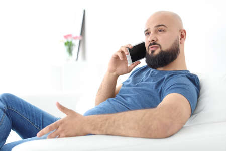 Portrait of young man talking on mobile phone on sofa