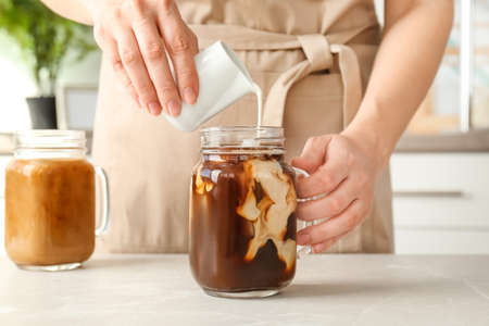Woman pouring milk into mason jar with cold brew coffee on table