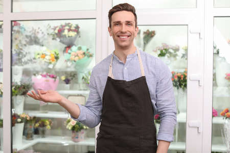 Handsome male florist in apron at workplace
