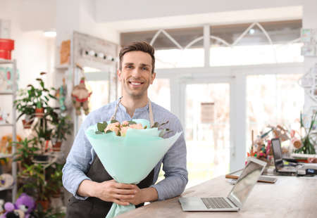 Male florist holding bouquet flowers at workplace