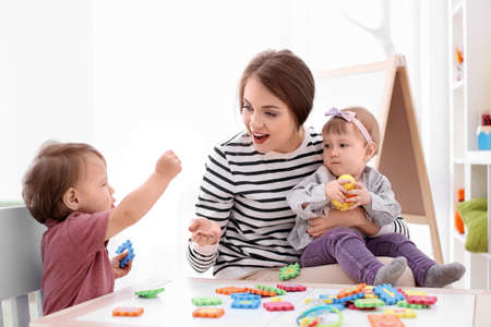 Photo pour Young nanny playing with cute little children at table, indoors - image libre de droit