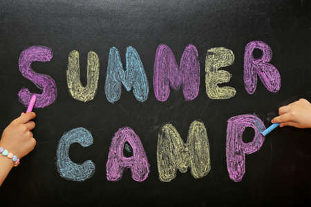 Children writing SUMMER CAMP with colorful chalk on blackboard, closeup