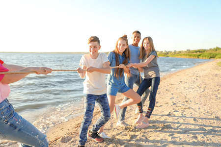 Photo for Group of children pulling rope during tug of war game on beach. Summer camp - Royalty Free Image