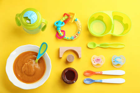 Flat lay composition with baby food and accessories on color background