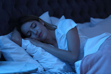 Photo for Young woman sleeping in bed at night. Sleeping time - Royalty Free Image
