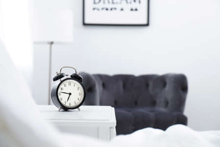 Analog alarm clock on table in bedroom. Time of day