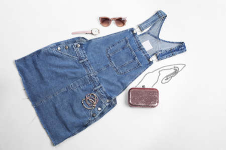 Flat lay composition with jean overall dress and accessories on white background