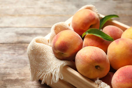 Wooden crate with fresh sweet peaches on table, closeup