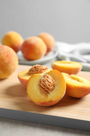 Wooden board with fresh sweet peaches on table, closeup