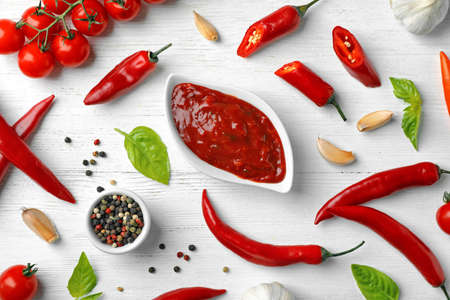 Flat lay composition with gravy boat of hot chili sauce and different spices on light background