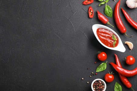 Flat lay composition with gravy boat of hot chili sauce and different spices on dark background