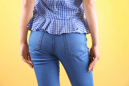 Woman in stylish blue jeans on color background