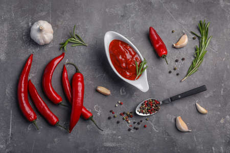 Flat lay composition with chili sauce and different spices on dark background