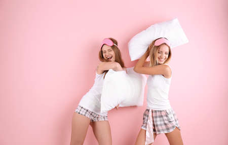 Two young women having pillow fight against color background