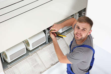 Photo pour Young male technician repairing air conditioner indoors - image libre de droit