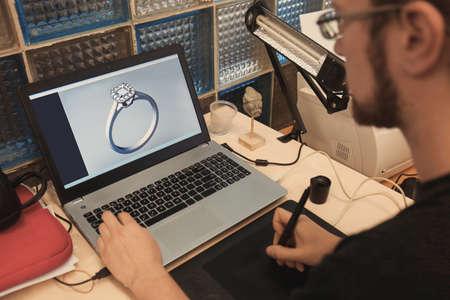 Photo pour Jewelry designer working on laptop, closeup - image libre de droit