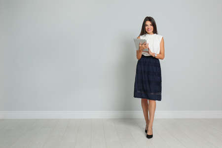 Photo for Beautiful woman with tablet wearing office clothes against gray wall. Space for text - Royalty Free Image