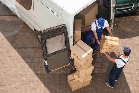 Photo pour Male movers unloading boxes from van outdoors, above view - image libre de droit