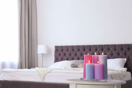 Burning candles on table in light bedroom