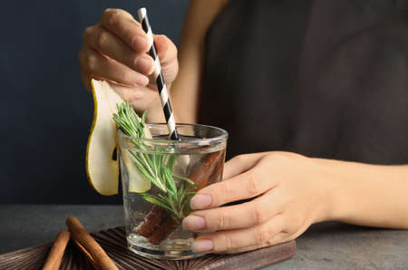 Woman holding glass cocktail with rosemary on table, closeup