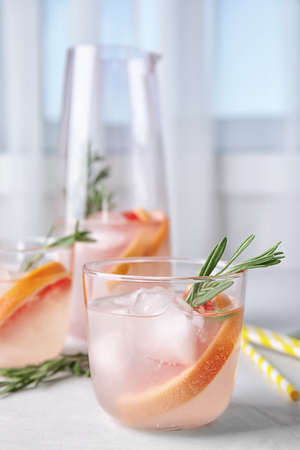Refreshing grapefruit cocktail with rosemary on table