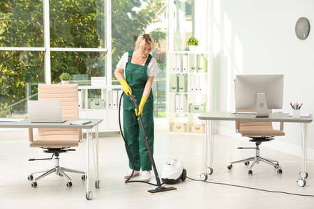 Photo pour Female janitor in uniform cleaning office floor - image libre de droit