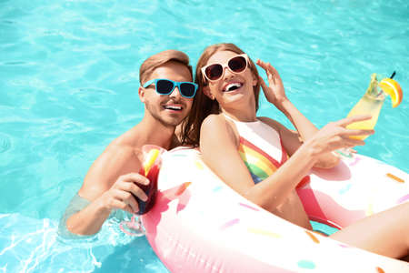 Photo pour Young couple with cocktails in pool on sunny day - image libre de droit