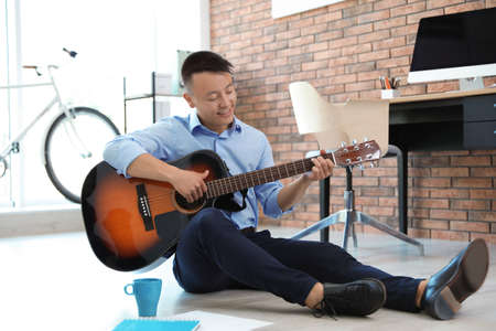 Photo pour Happy young businessman playing guitar during break in office. Peaceful moment - image libre de droit