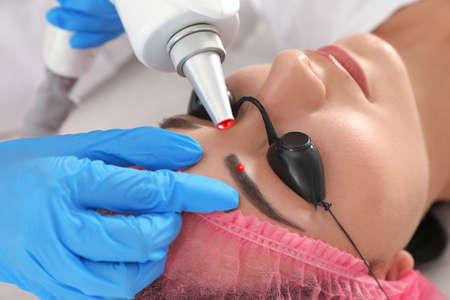 Photo pour Woman undergoing laser tattoo removal procedure in salon, closeup - image libre de droit