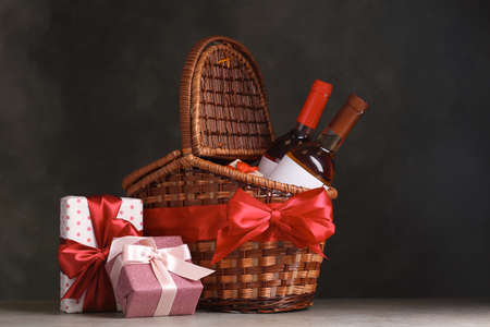 Foto de Festive basket with bottles of wine and gifts on table against dark background - Imagen libre de derechos