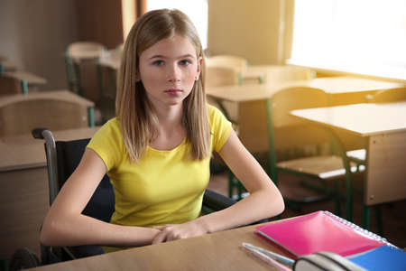 Photo pour Sad teenage girl in wheelchair at desk in classroom - image libre de droit