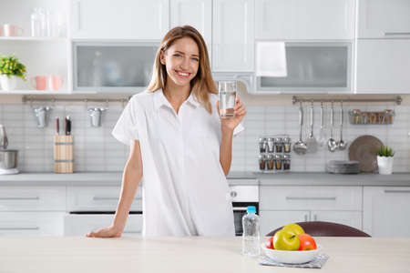 Photo for Young woman holding glass with clean water in kitchen - Royalty Free Image