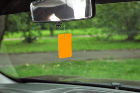 Photo pour Air freshener hanging in car against windshield - image libre de droit