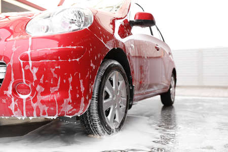 Photo for Red auto with foam at car wash. Cleaning service - Royalty Free Image