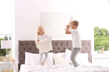 Photo pour Happy children having pillow fight on bed at home - image libre de droit