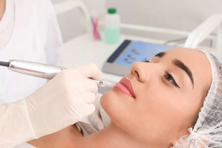 Photo for Young woman undergoing procedure of permanent lip makeup in tattoo salon, closeup - Royalty Free Image