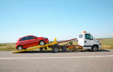 Photo pour Tow truck with broken car on country road - image libre de droit