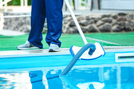 Photo for Male worker cleaning outdoor pool with underwater vacuum - Royalty Free Image