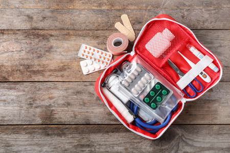 Foto de Flat lay composition with first aid kit and space for text on wooden background - Imagen libre de derechos