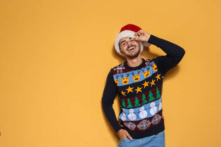 Foto de Young man in Christmas sweater and hat on color background. Space for text - Imagen libre de derechos