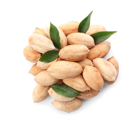 Heap of pecan nuts in shell and leaves on white background, top view