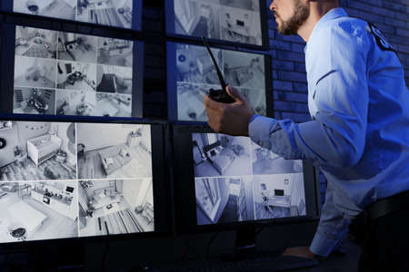Photo pour Male security guard with portable transmitter monitoring modern CCTV cameras indoors - image libre de droit
