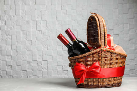 Foto de Gift basket with bottles of wine on light background. Space for text - Imagen libre de derechos