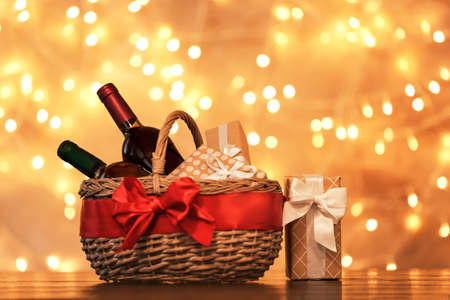 Foto de Gift basket with bottles of wine against blurred lights. Space for text - Imagen libre de derechos