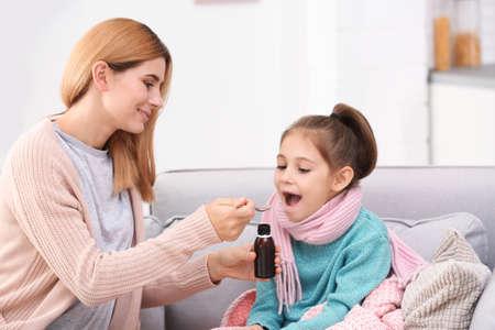Photo pour Mother giving daughter cough syrup on sofa at home - image libre de droit